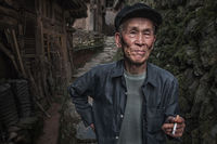 asia,asian,china,chinese,da zhai,da zhai terrace fields,dazhai,elderly,environmental portait,hat,longji,longji rice terraces,longsheng,male,man,old,older,people,portrait,smoking,standing,terraces,tian