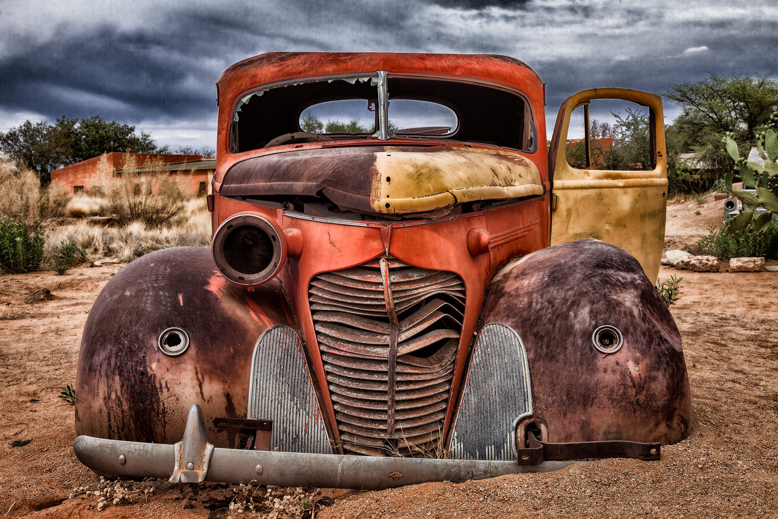 Dilapidated classic car at the edge of the Namibian desert