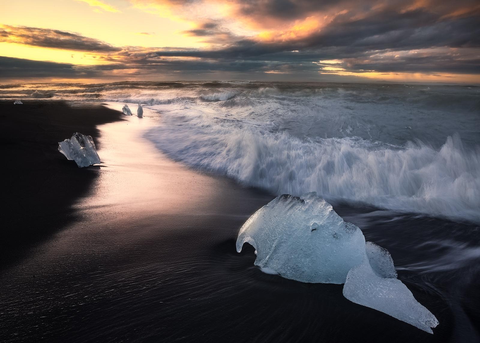 Sunrise behind Icebergs on Iceland's black sand beach Breidamerkursandur.