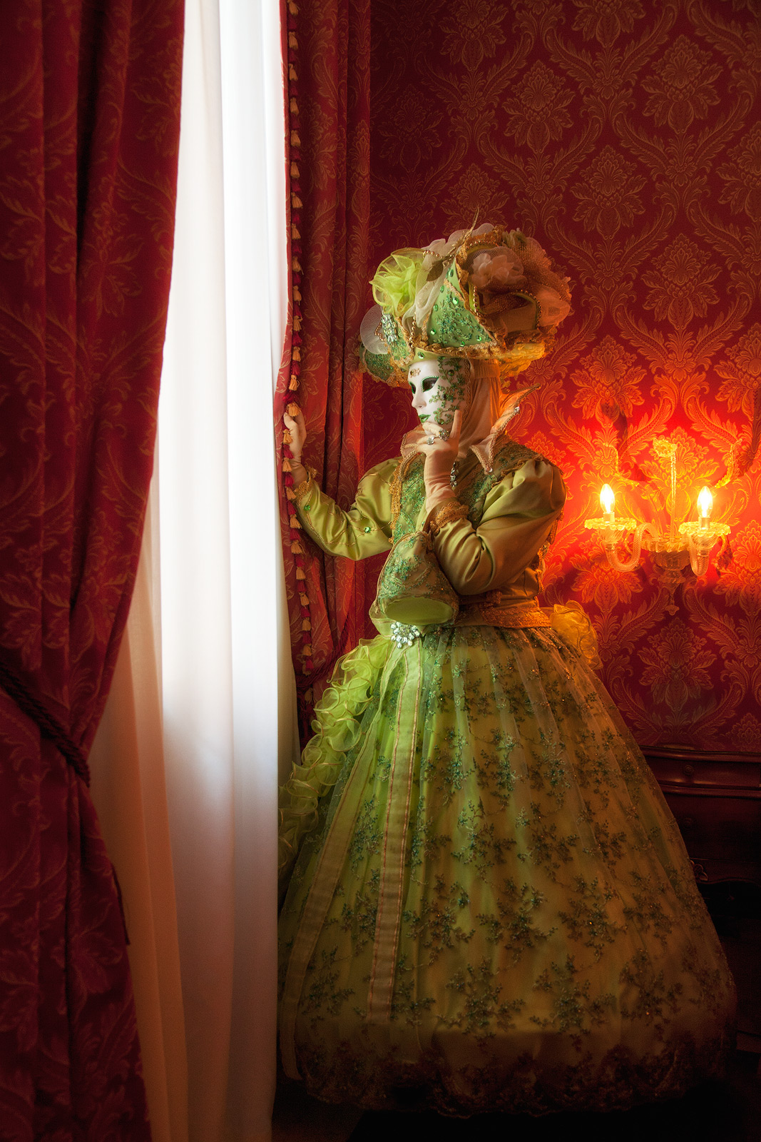 Green costumed model looking out of her hotel window in Venice