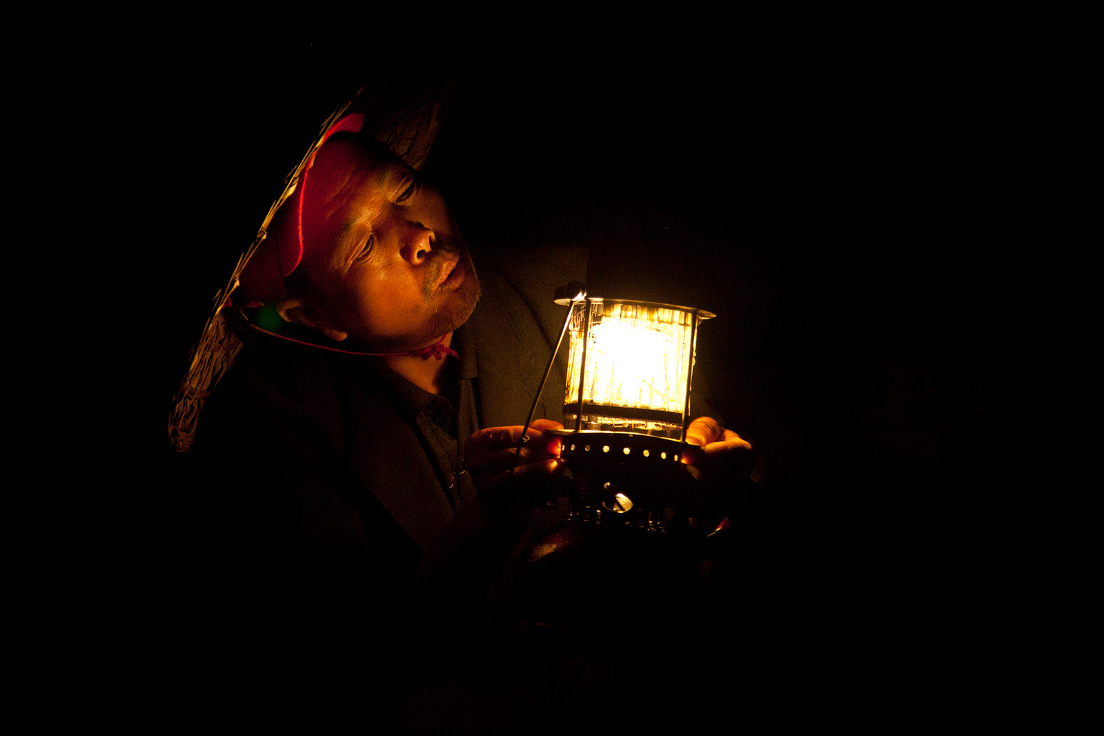 Close-up of Chinese fisherman wearing a hat and holding a lantern