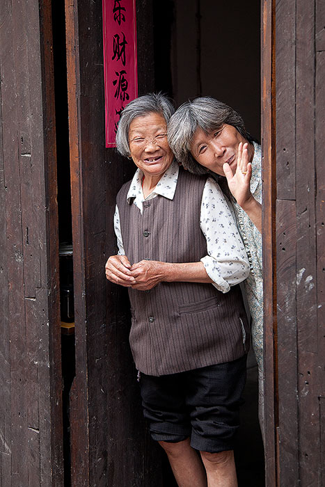 Two friendly Chinese women in a doorway