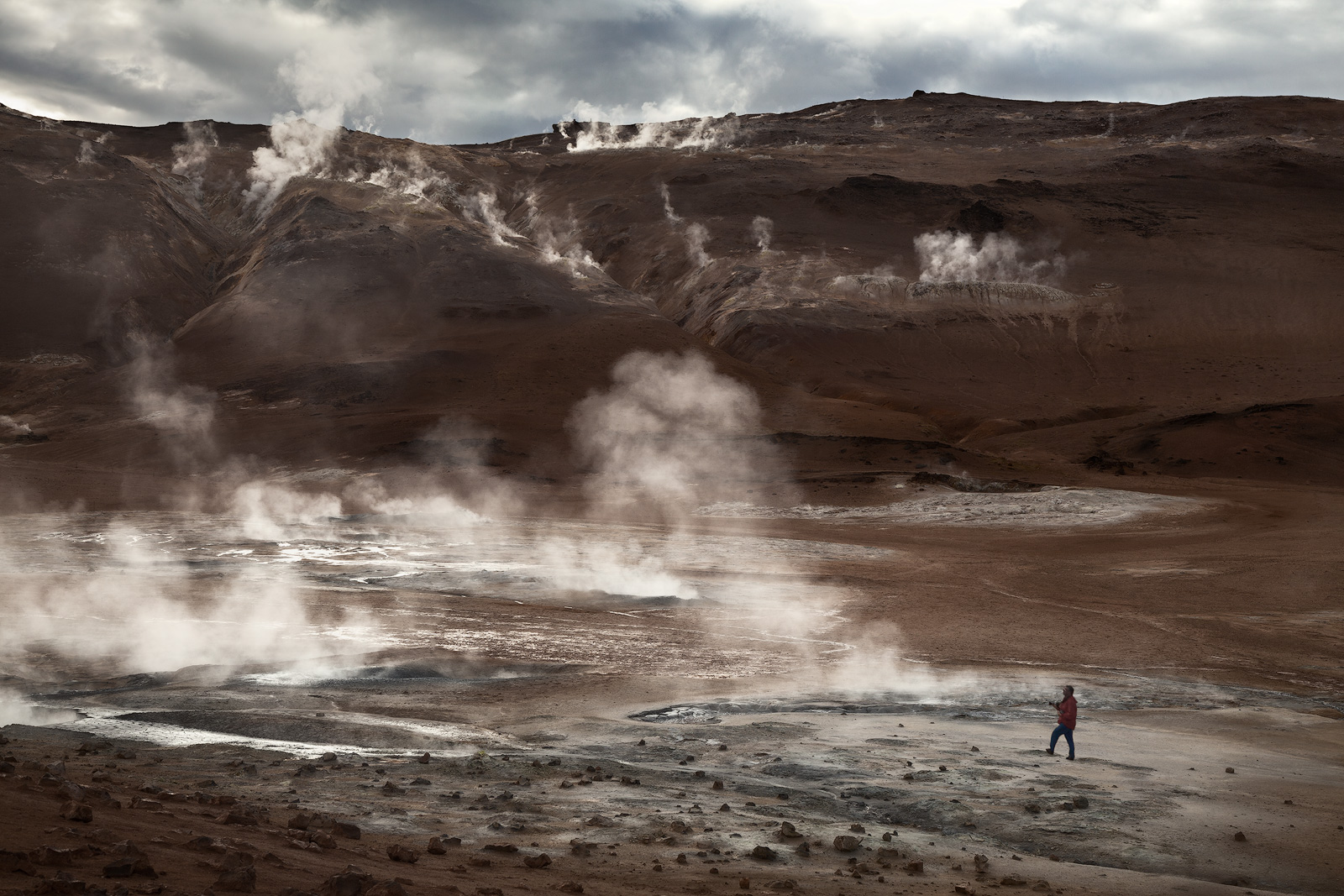 A lone hiker walks through one of Iceland's geothermal fields