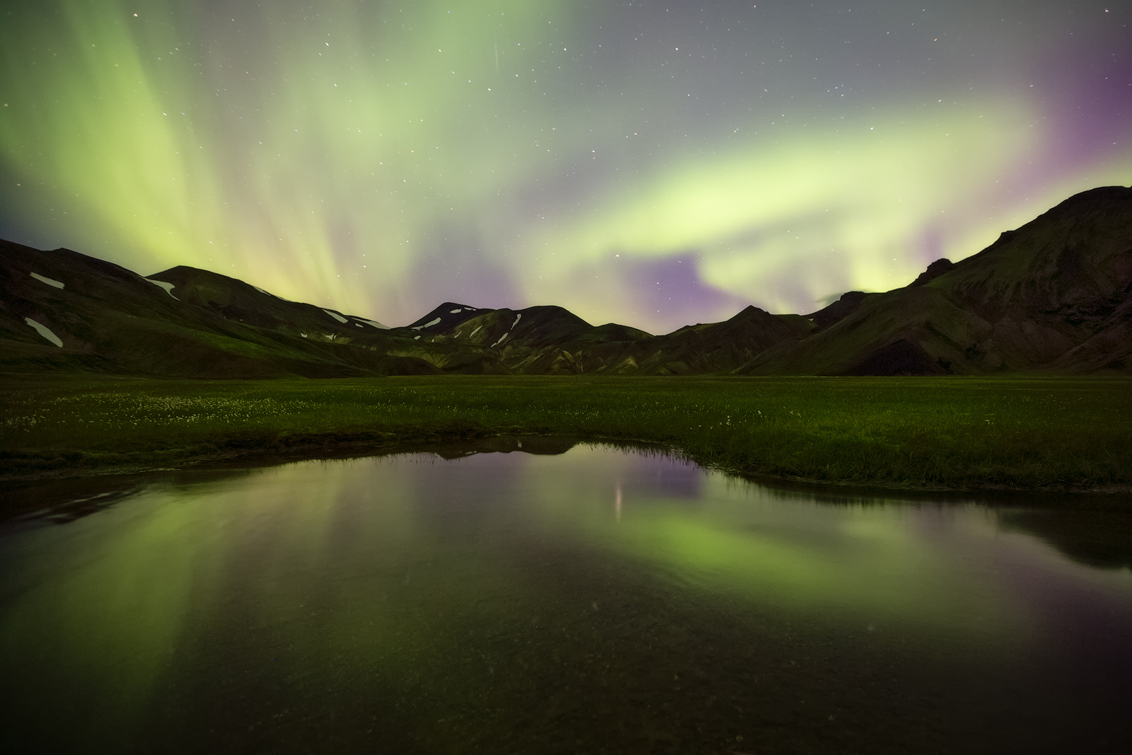 Northern lights over a small pond in Landmannalaugar