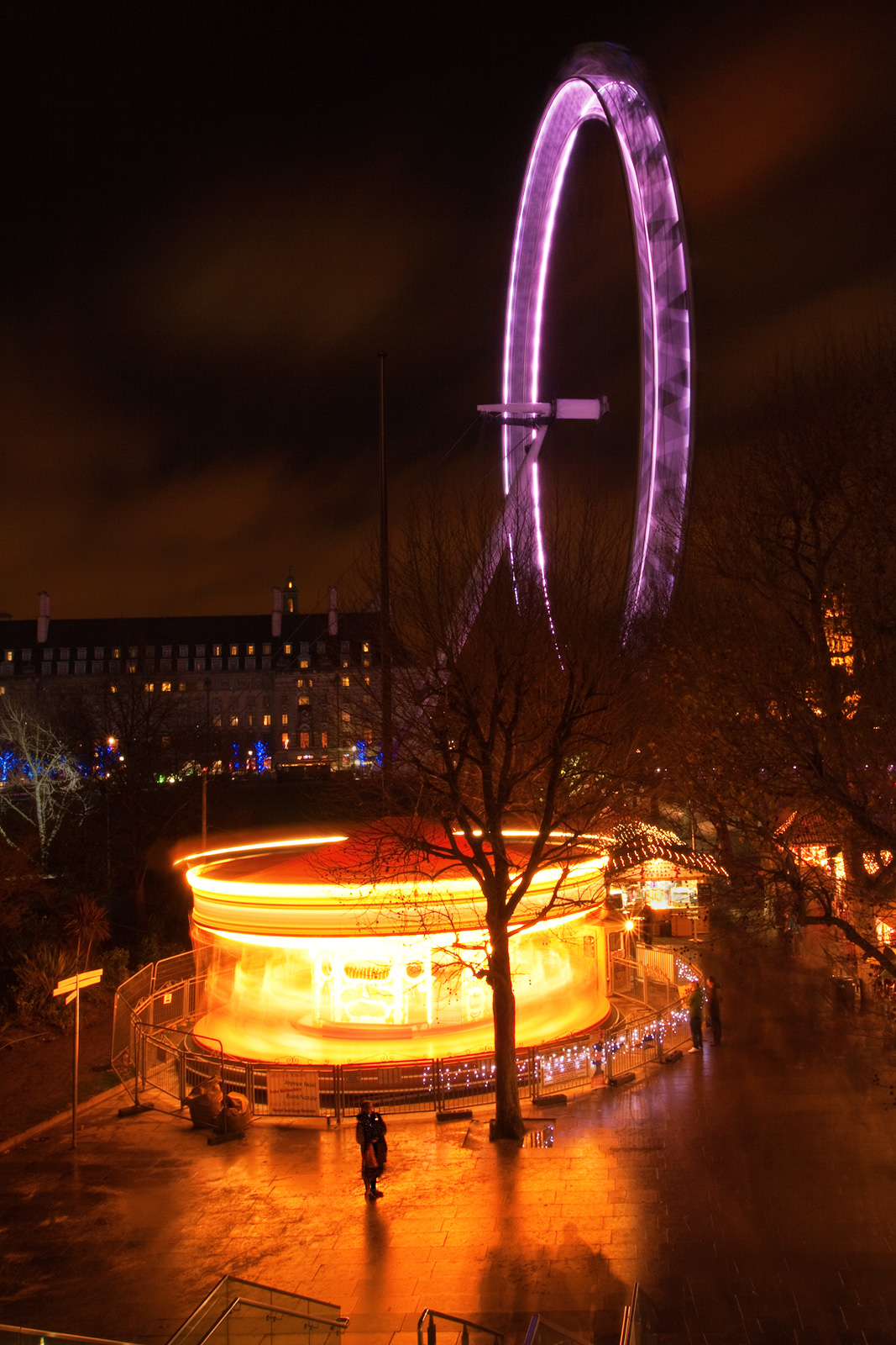 Silhouette near a merry-go-round and the London Eye