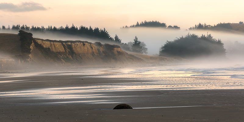 Fog rolling over the cliffs on Moeraki beach.