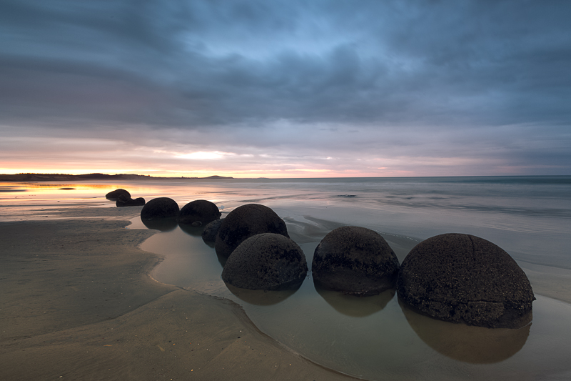 The iconic Moeraki Boulders with low-angled sunlight in the background.