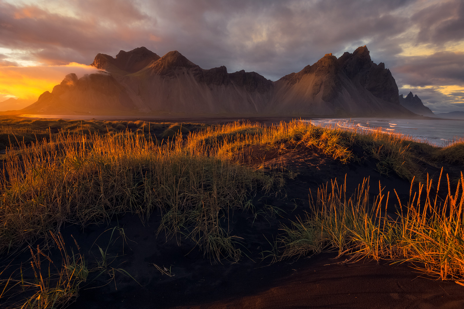 Glowing fields from low-angled sidelight in front of Iceland's Vestrahorn Mountain.