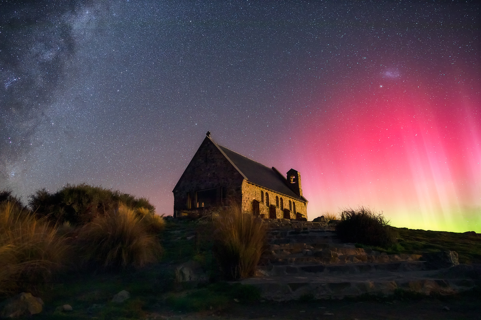 A stone church surrounded by beams from the southern lights (Aurora australis) on one side and the Milky Way on the other.