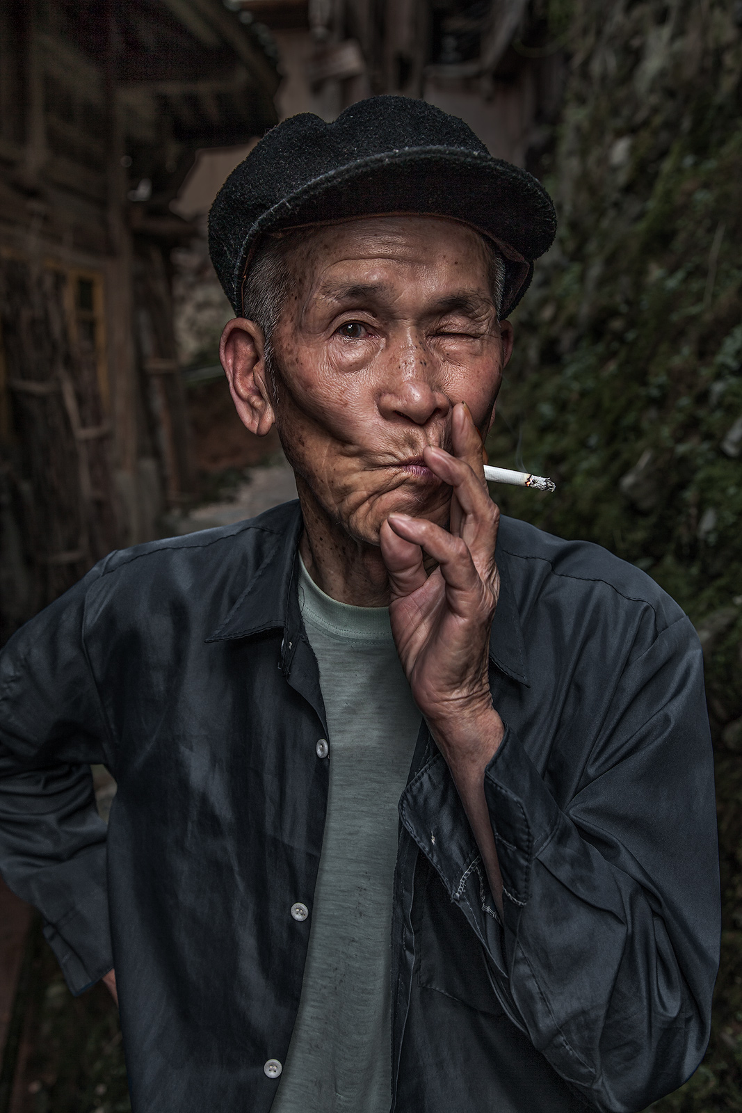 An older Chinese man having a smoke in front of his house.