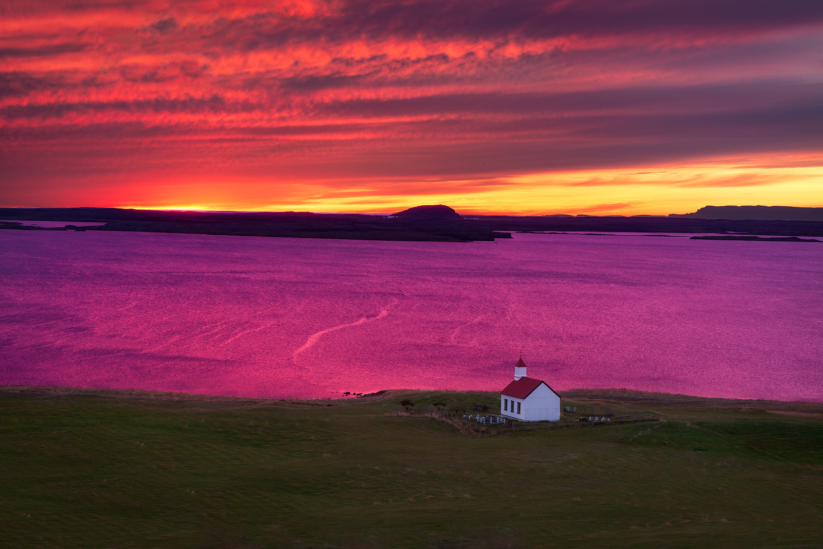 Red and white church over a lake turned purple at sunset