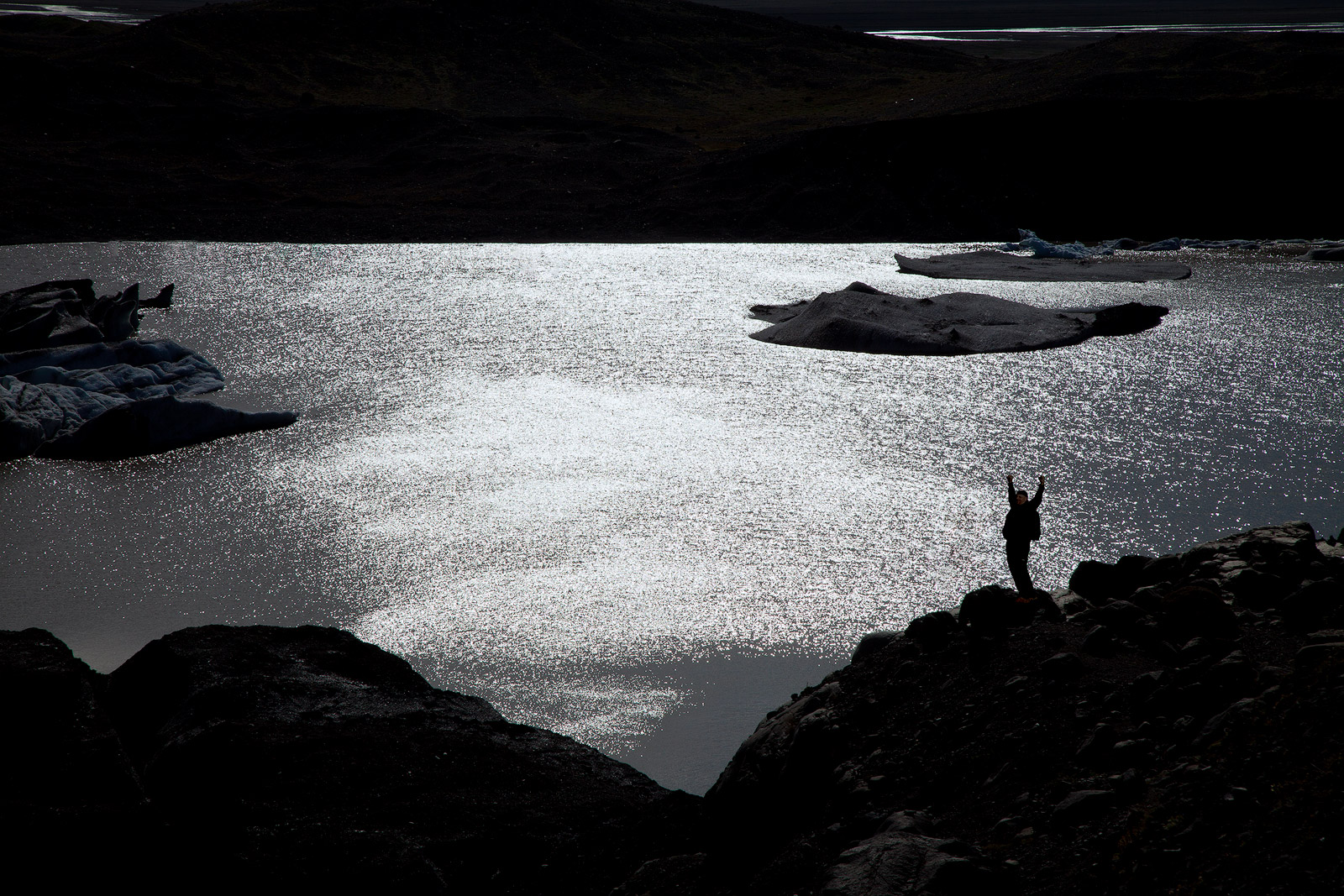 Silhouette of a hiker in front of a lake formed by glacier runoff