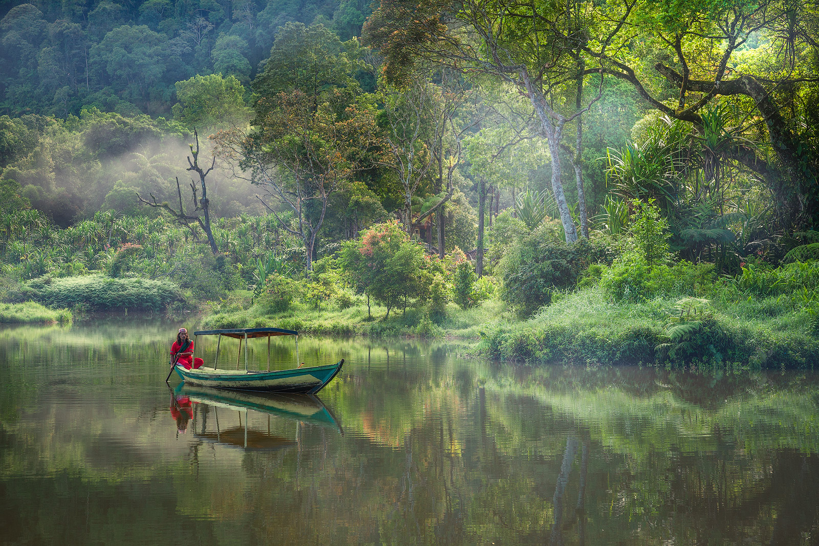 An Indonesian man takes an early morning boat ride on a remote lake.