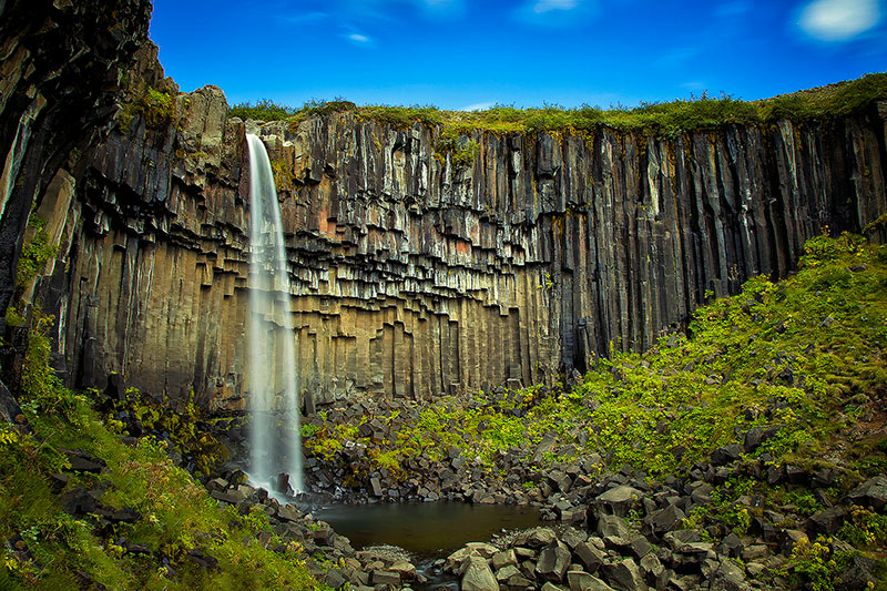 Blue sky over a waterfall with basalt columns