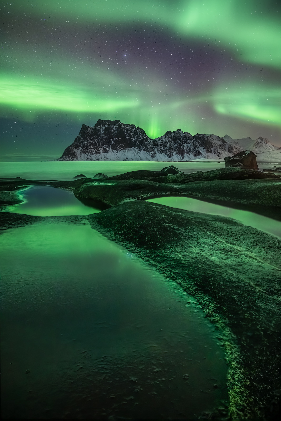 A nice aurora reflecting in foreground pools along a coastline in Lofoten.