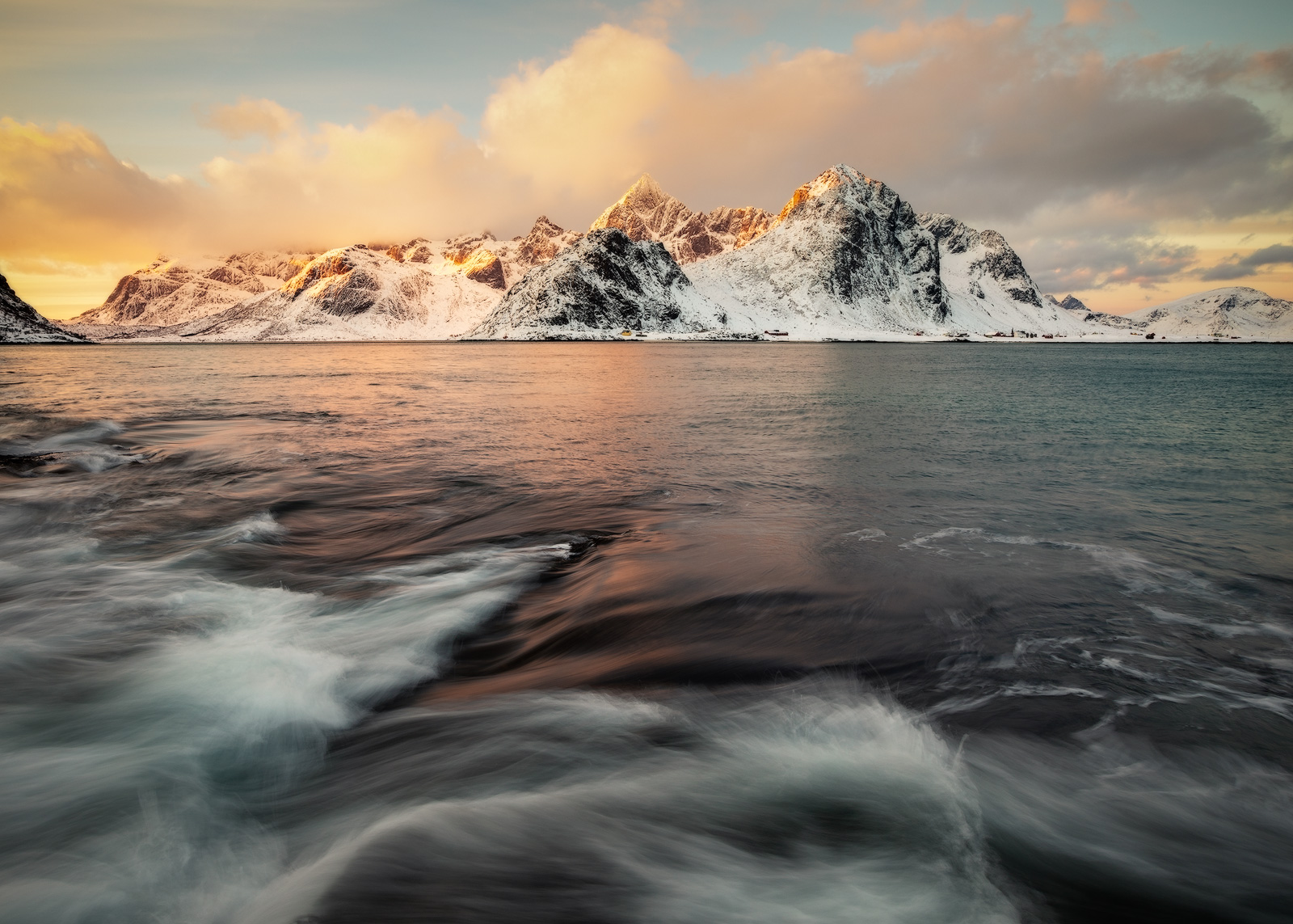 Waves moving across the shore as a brilliant sunrise lights up the distant mountain.